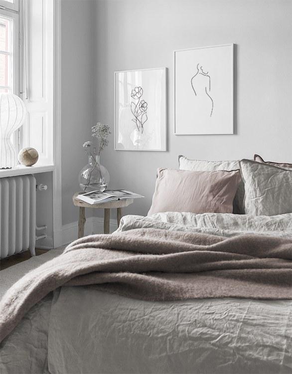 Romantiskt sovrum med ljusrosa toner och minimalistiska tavlor