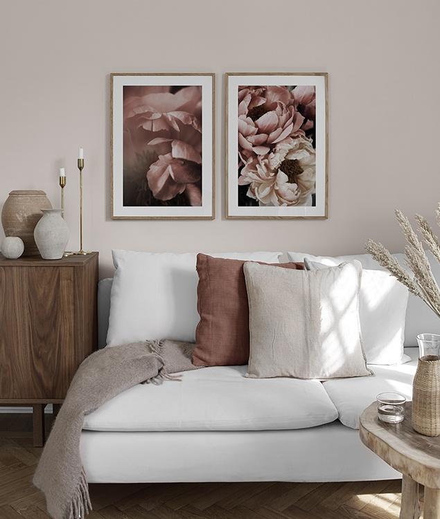 Inred vardagsrummet med mjuka rosa färger och blomtavlor
